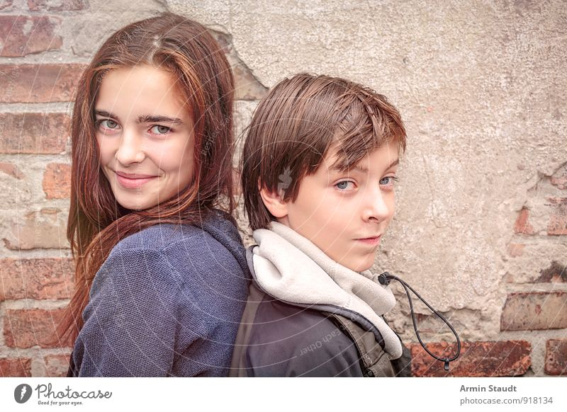 Porträt zweier Geschwister, Rücken an Rücken Lifestyle Winter Mensch maskulin feminin Bruder Schwester Jugendliche 2 13-18 Jahre Kind Mauer Wand Lächeln