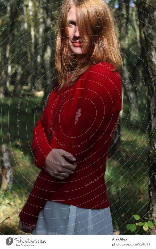 Junge Frau in rotem Pullover und weißem Rock steht im Wald und lächelt Ausflug Abenteuer Jugendliche 18-30 Jahre Erwachsene Natur Schönes Wetter Baum rothaarig
