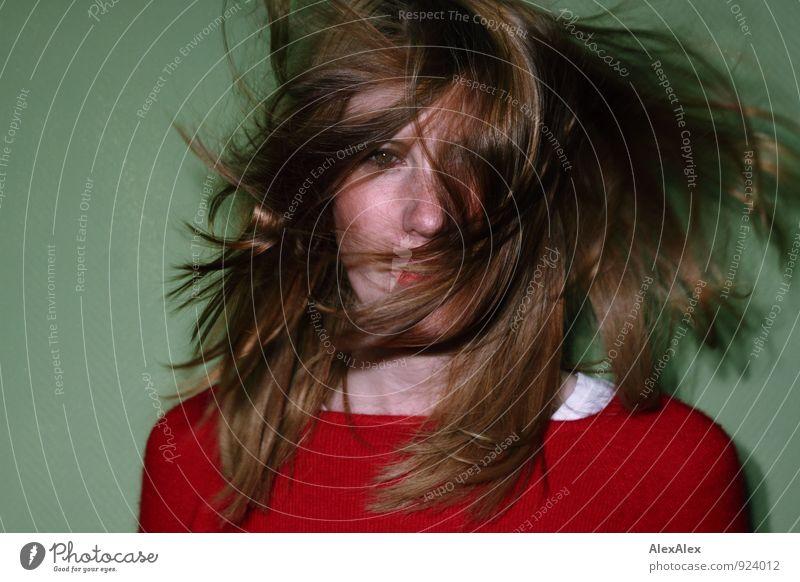 Frau vor grüner Wand mit rotem Pullover hat um das Gesicht wehendes, rotes Haar Lifestyle Stil Junge Frau Jugendliche Haare & Frisuren 18-30 Jahre Erwachsene