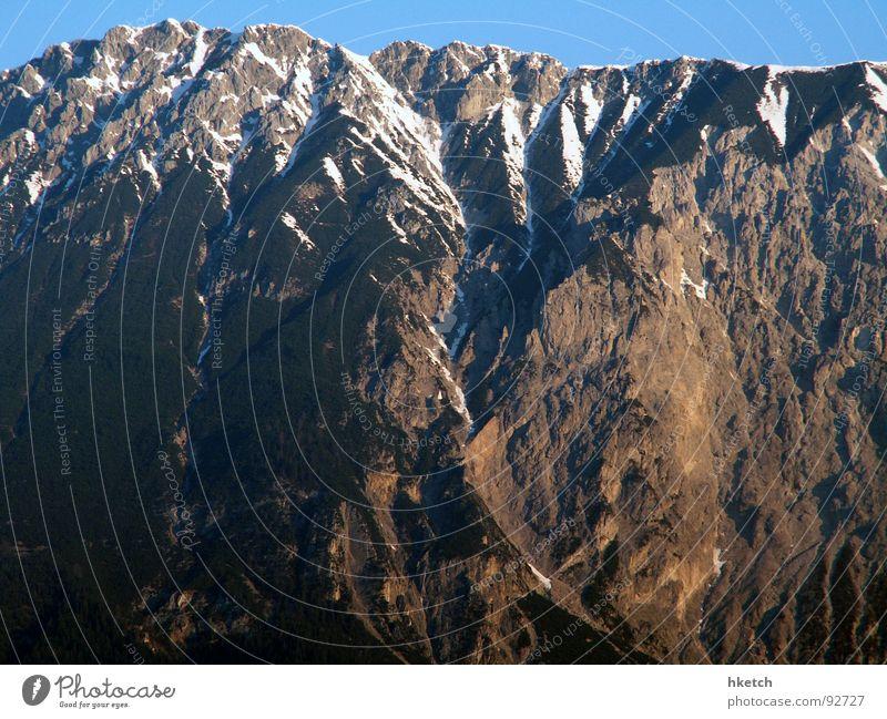 Echo des Bergrufs Winter Bergkette Schneedecke Sonnenstrahlen alpin Gipfelkreuz wandern Luft Berghütte Wanderschuhe Horizont Österreich Schneeschmelze
