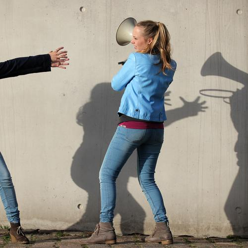 . Mensch Wand feminin Wege & Pfade Mauer Kraft blond Wut Jeanshose Jacke Mut langhaarig selbstbewußt kämpfen Willensstärke Zopf