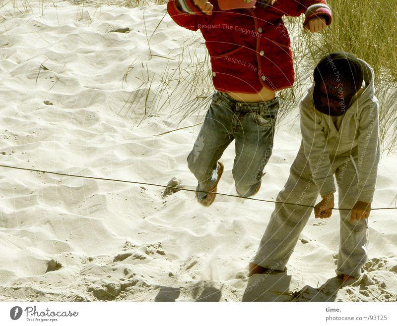 Übersprungshandlung Farbfoto Gedeckte Farben Außenaufnahme Tag Freude Freizeit & Hobby Spielen Ferien & Urlaub & Reisen Strand Kind Mädchen Junge Geschwister