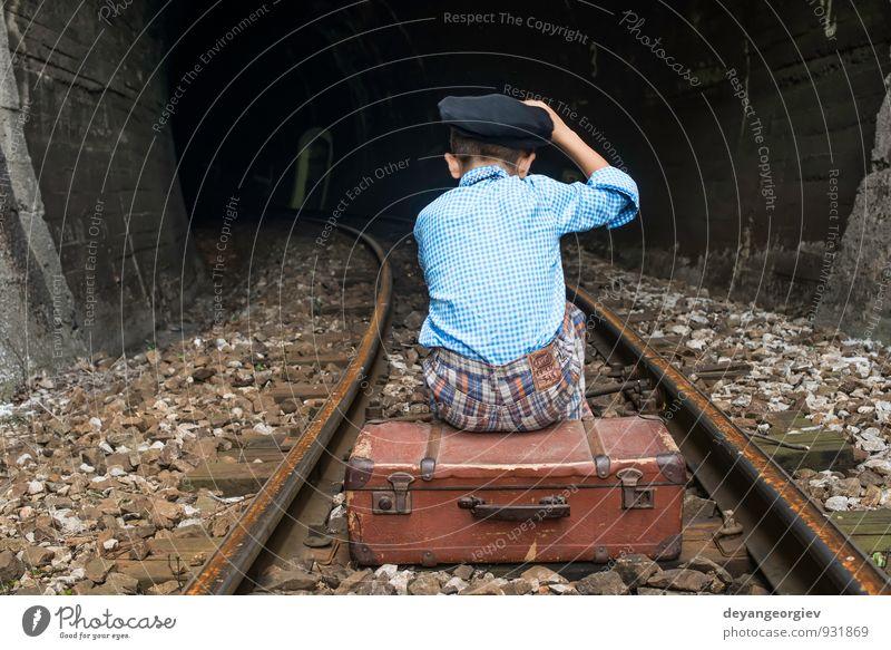Kind in Vintage-Kleidung sitzt auf der Eisenbahnstrecke. Ferien & Urlaub & Reisen Ausflug Mensch Mädchen Junge Kindheit Natur Verkehr Koffer fallen sitzen