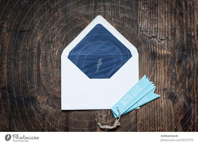 Weisser Briefumschlag auf Holztruhe mit blauen Anhängern Design Valentinstag Muttertag Geburtstag Business Musiknoten Schreibwaren Papier Zettel Liebe Abstract