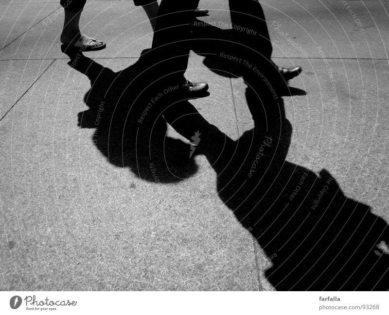 Passanten Fußgänger Licht dunkel Stadt gehen Verkehrswege Beine Schatten Schwarzweißfoto Bodenbelag Straße laufen