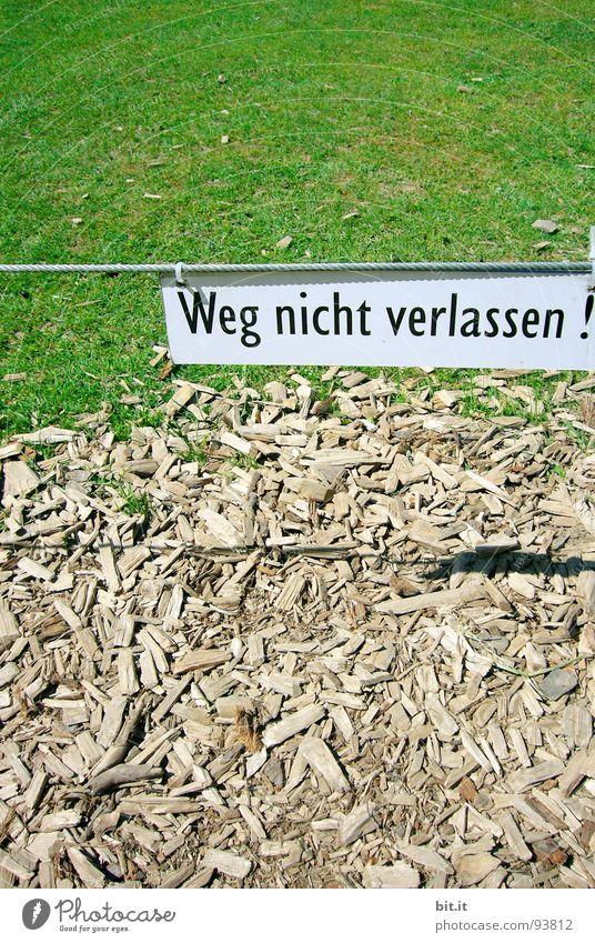 Weg nicht verlassen, geschrieben auf weissem Schild in Schwarz, über einer Wiese in der Natur Gras Wege & Pfade Zeichen Schriftzeichen Schilder & Markierungen
