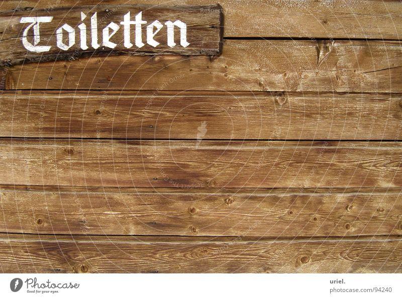 Jeder muss mal... Holz Wand braun Pissoir Skihütte Südtirol Hinweisschild Bad Gastronomie Lamelle Holzbrett Schriftzeichen Toilette Wegweiser Hütte