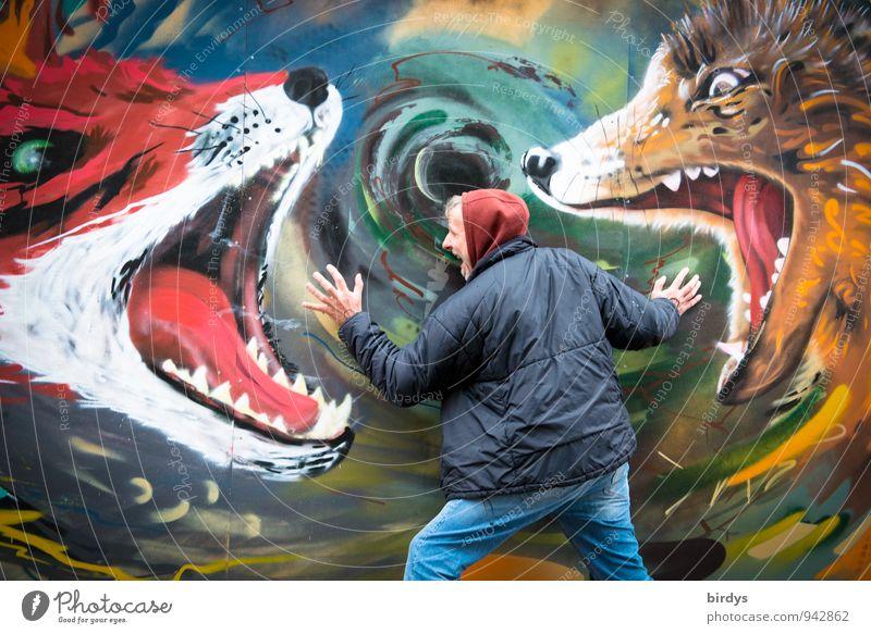 Mann in Hoody  und Jacke fühlt sich von wilden Tieren angegriffen welche auf einer Wand aufgemalt sind. Symbolbild, Alptraum Todesangst Erwachsene Angst 1
