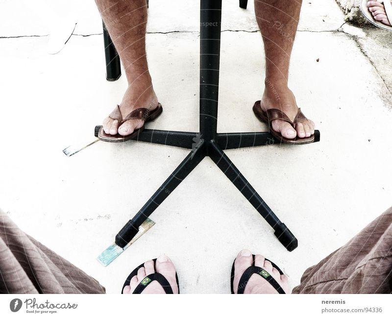 Kooperation Farbfoto Außenaufnahme Nahaufnahme Tag Sommer Tisch Mann Erwachsene Beine Fuß 2 Mensch Hose Flipflops Stein Kommunizieren sitzen fest braun grau