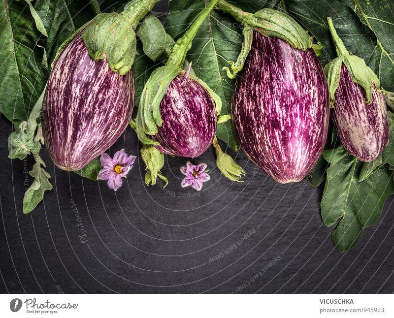 Auberginen mit Blättern und Blüten auf dunklen Schiefer Tisch Lebensmittel Gemüse Bioprodukte Vegetarische Ernährung Diät Lifestyle Design Gesunde Ernährung
