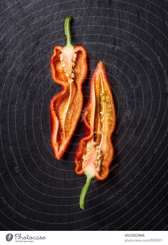 Halbierte rote Paprika. Lebensmittel Gemüse Ernährung Bioprodukte Vegetarische Ernährung Diät Lifestyle Natur schwarz Hintergrundbild Chili Vitamin Teilung lang