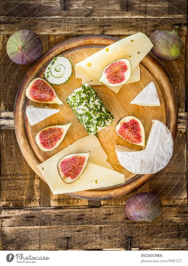 Runde SchneideBrett mit Käse und Feigen grün rot gelb Leben Holz braun Lebensmittel rosa Lifestyle Wohnung Frucht Design Perspektive Ernährung Bioprodukte
