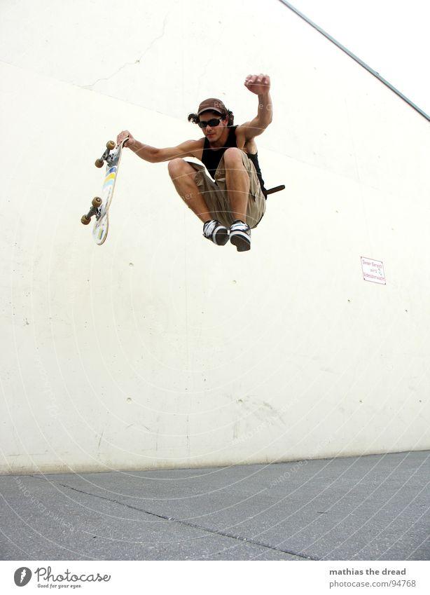 Flugversuch Sport belasten Gesundheit Freizeit & Hobby springen Skateboarding Beton Wand Licht Sonnenlicht Mann Junger Mann Mütze Shorts Sprungkraft gefährlich
