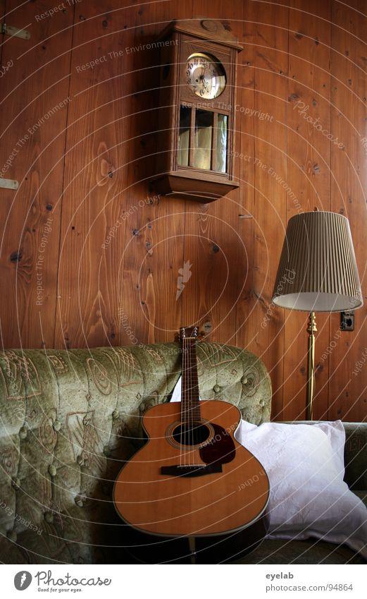 Gemütlichkeit ist keine Frage der Einstellung Wand Holz Wandtäfelung Westerngitarre Sofa Sitzgelegenheit bequem Lampe Stehlampe Wanduhr Uhr analog Kissen