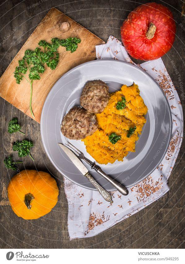 Kürbis Püree mit Fleisch Buletten. Natur Winter dunkel Gesunde Ernährung gelb Holz Lebensmittel Metall Gemüse Bioprodukte Geschirr Teller Abendessen