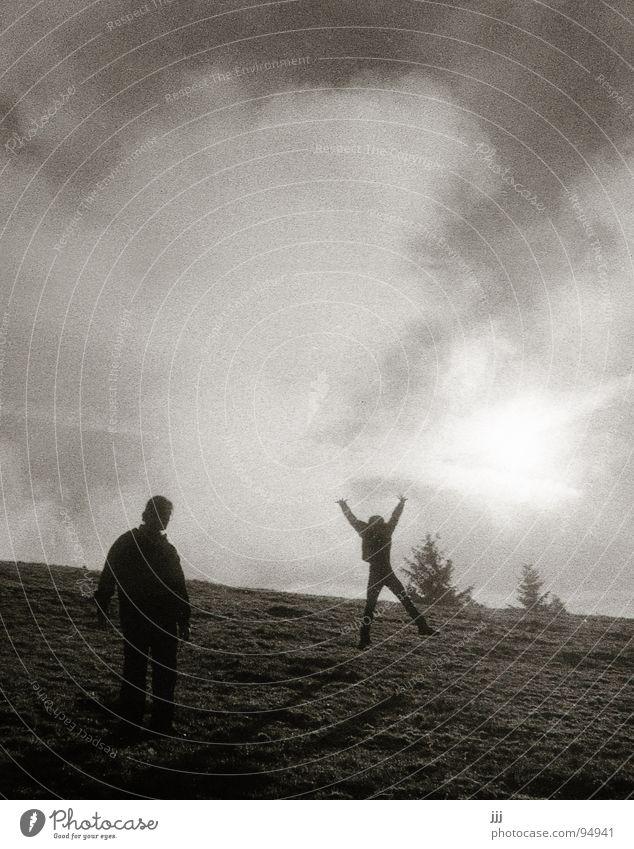 spontane Eruption springen Hügel Wiese Streifen Baumkrone bereit Berghang Freude Schwarzweißfoto Vorsprung Sonne zwei Menschen X hoch Silhouette Schatten wups