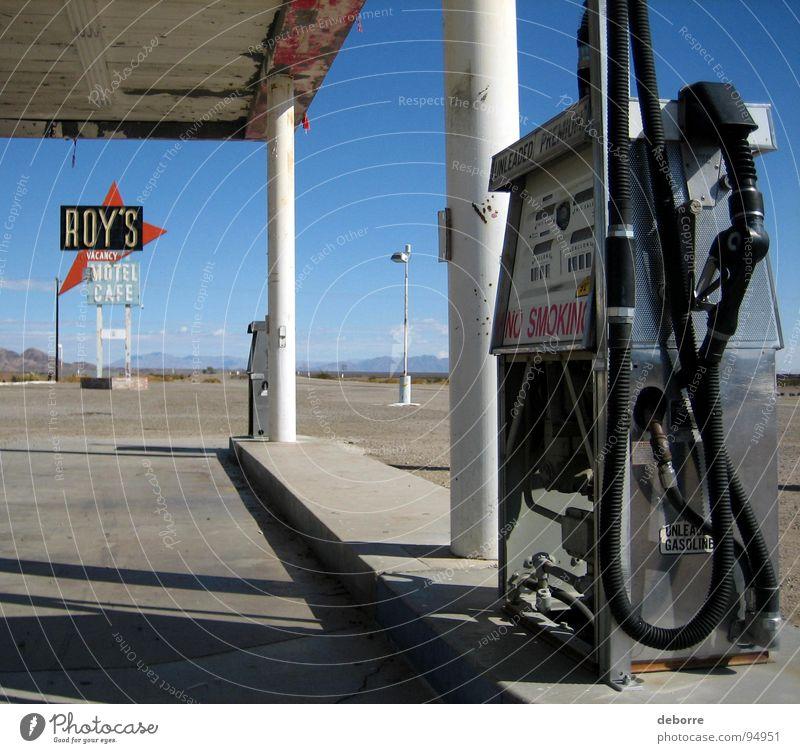 """Retroamerikanische Tankstelle an der Route 66 mit dem Schild """"Roy's Motel"""" im Hintergrund. Benzin Rohstoffe & Kraftstoffe tanken Amerika Diesel Erdöl grau"""