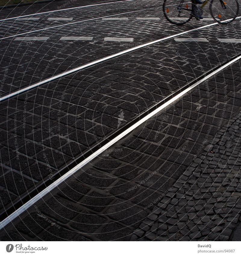 18:07 Asphalt Kopfsteinpflaster Fahrradweg Gleise weiß grau schwarz heimwärts Feierabend Verkehrswege Schwarzweißfoto Straße Wege & Pfade pseudo-schwarzweiß