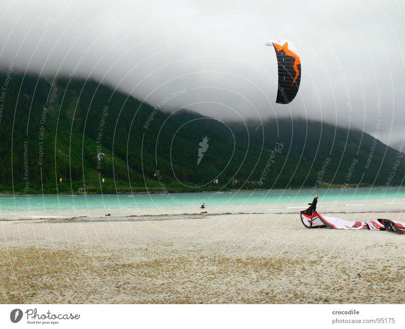 kitesurfing in austria Kiter Surfer See Achensee Bundesland Tirol kalt Wind Wolken Leidenschaft dunkel Strand Schnur Wald Sport gefährlich Mann Extremsport