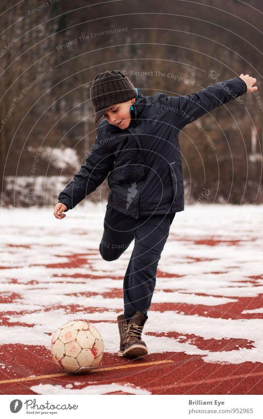 Junge kickt Fussball Mensch Kind Freude kalt Leben Bewegung Gefühle Schnee natürlich Sport maskulin Lifestyle Eis Zufriedenheit authentisch