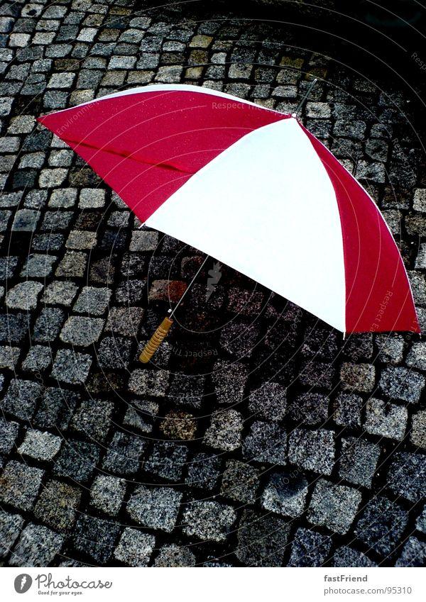 Regenkämpfer rot weiß nass Griff Regenschirm Herbst Wasser Stein Mineralien Gewitter umbrella rain pavement wet red white protection Pflastersteine
