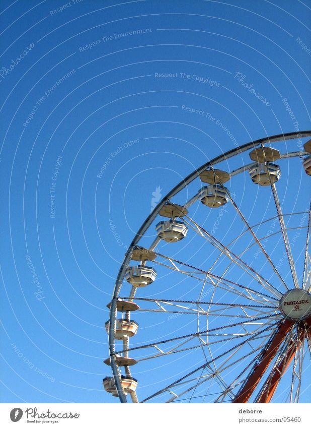 Der Blick hinauf zu einem Riesenrad mit blauem Himmel dahinter. gelb groß Jahrmarkt Karussell rund Freude Dinge hoch kreisen