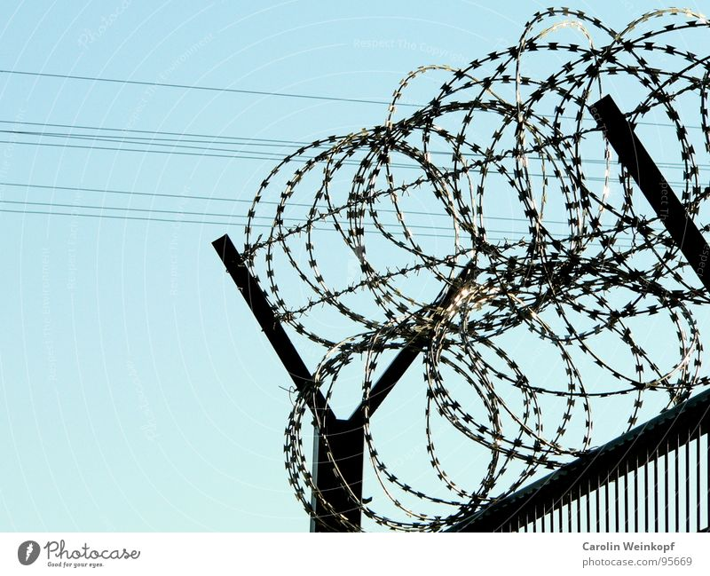 Antidemonstrantischer Schutzwall. Zaun Stacheldraht Käfig G8 Gipfel gefangen aussperren Nationale Sicherheit grau geschlossen Sperrzone Himmel blau eingezäunt
