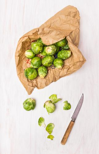 Rosenkohl in Papiertüten auf weißen Holztisch Natur Blatt Winter Stil Gesundheit Lebensmittel Design Ernährung Tisch Reinigen Gemüse Bioprodukte Messer Diät