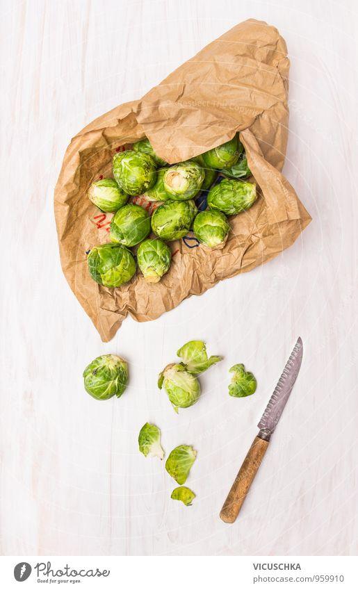 Rosenkohl in Papiertüten auf weißen Holztisch Natur Blatt Winter Stil Gesundheit Lebensmittel Design Ernährung Tisch Papier Reinigen Gemüse Bioprodukte Messer Diät Tüte