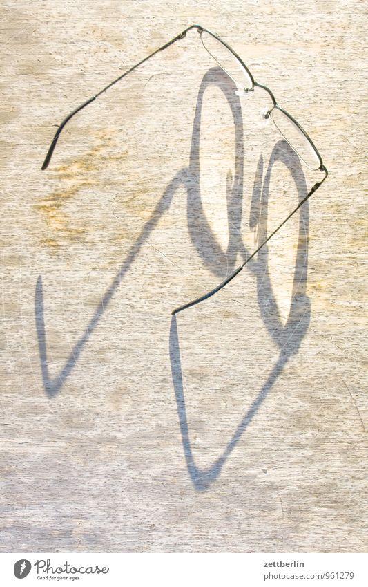 Brille durchsichtig Glas Holz Licht Linse Optik Optiker Schatten Blick Tisch Vogelperspektive Sonne Textfreiraum Hintergrundbild Kleiderbügel fein Draht