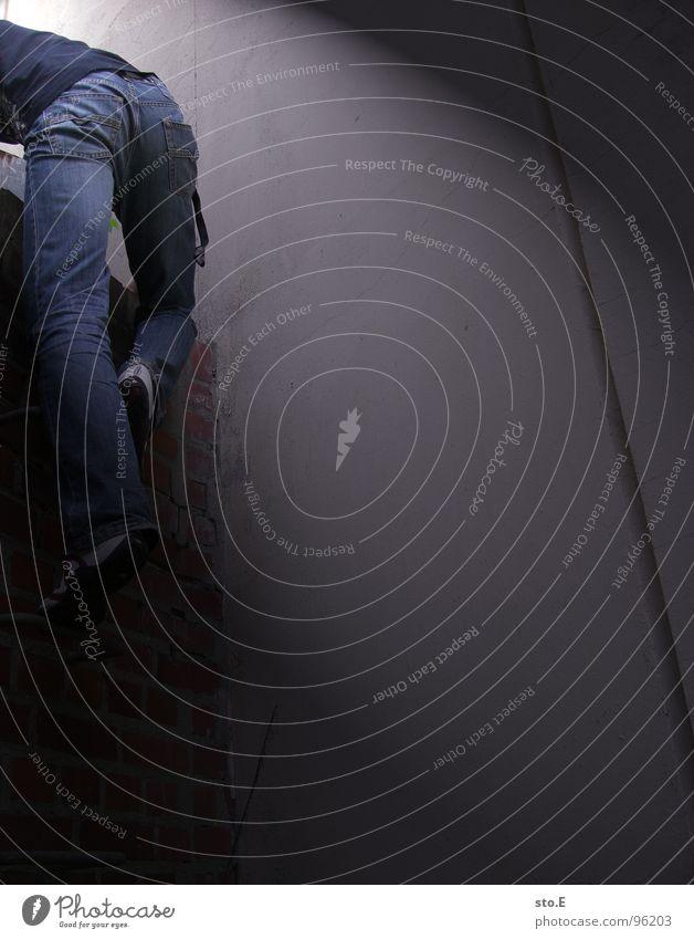 aim@ausbruchversuch Licht Körperhaltung Wand Mauer Nische Schacht Backstein Haus gefangen gestellt blenden aufsteigen steigend schwarz weiß T-Shirt Hose