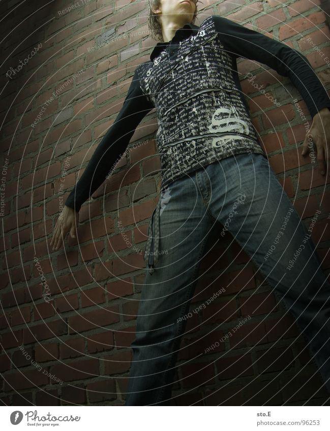 surrender@ausbruchversuch Licht Körperhaltung Wand Mauer Backstein Haus gefangen gestellt blenden stehen bewegungslos schwarz weiß T-Shirt Hose Hoppegarten