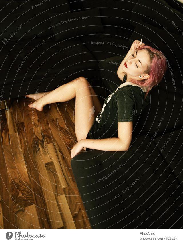 Rauchen nur im Sitzen Junge Frau Jugendliche Gesicht Beine 18-30 Jahre Erwachsene Wohnzimmer Sofa Holzfußboden T-Shirt Zigarette Barfuß langhaarig rosa sitzen