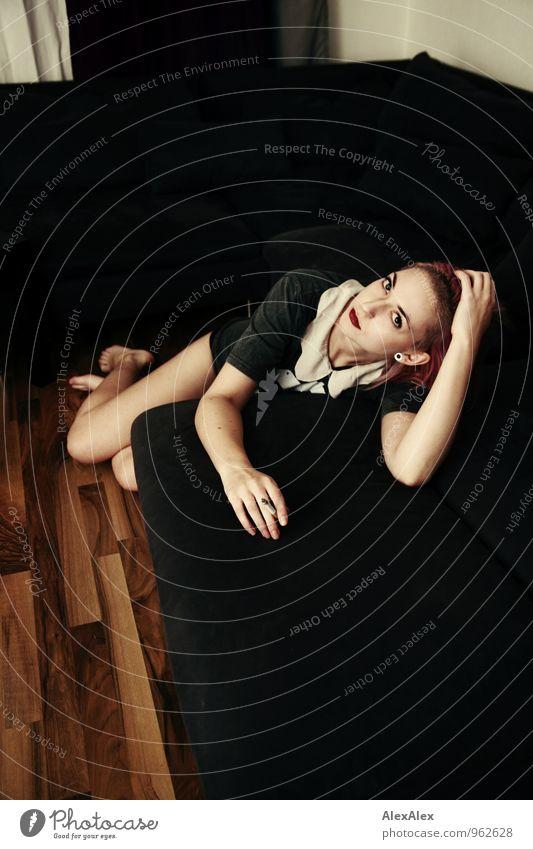junge Frau liegt barfuß auf eine Couch gelehnt und schaut in die Kamera Lifestyle elegant Stil Sofa Wohnzimmer Holzfußboden Nachtleben Junge Frau Jugendliche