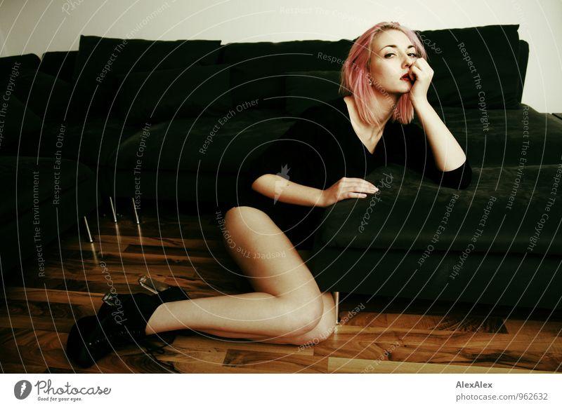 junge, langbeinige Frau mit pinken Haaren sitzt vor der Couch Häusliches Leben Wohnung Sofa Holzfußboden Junge Frau Jugendliche Gesicht Beine 18-30 Jahre