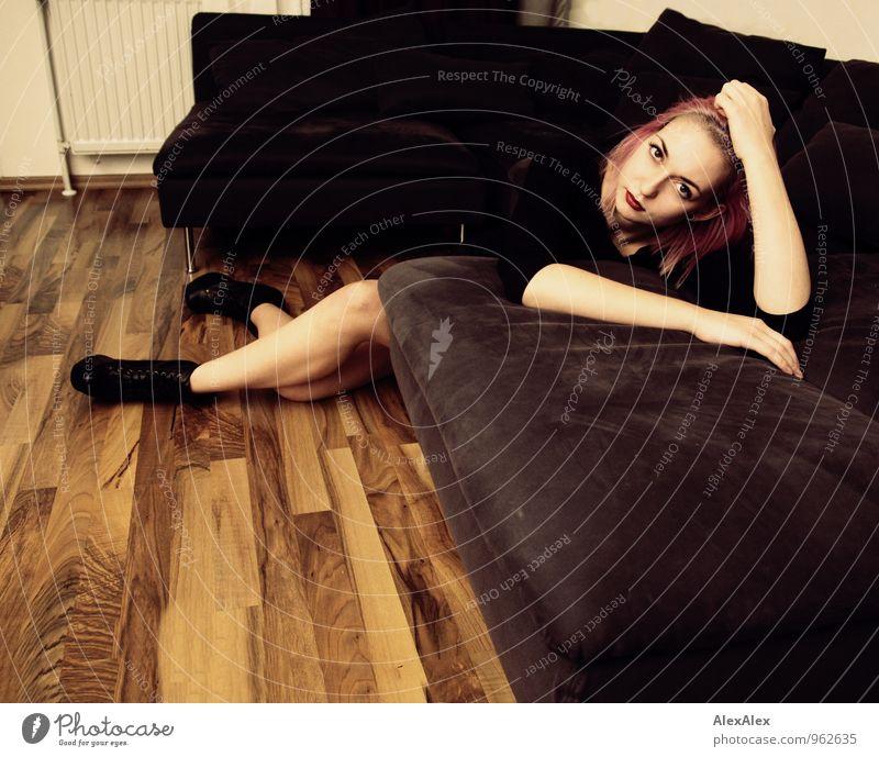 Junge Frau mit pinken Haaren liegt auf die Couch gelehnt Wohnung Sofa Wohnzimmer Holzfußboden Nachtleben Jugendliche Beine 18-30 Jahre Erwachsene T-Shirt