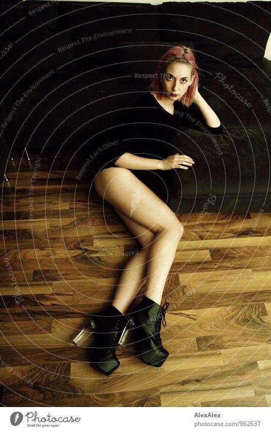 junge, langbeinige Frau mit pinken Haaren liegt in High Heels vor einer Couch elegant Stil Sofa Wohnzimmer Nachtleben Junge Frau Jugendliche Beine 18-30 Jahre