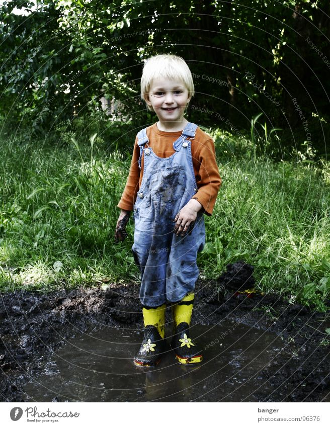 Matsch Pfütze Kind Gummi Stiefel nass Freude Wasser Regen dreckig Junge
