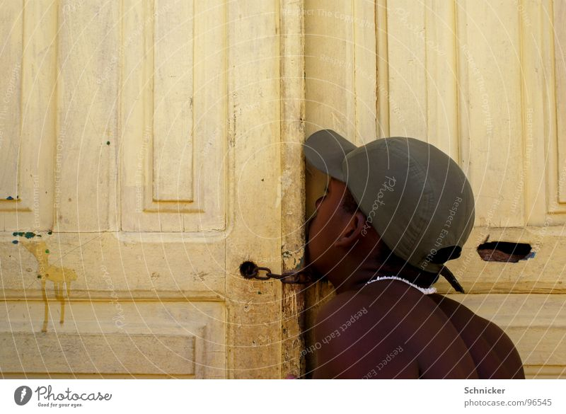 Der Gerüchteflüsterer Flüstern geheimnisvoll sprechen tratschen Mütze Brasilien Baseballmütze Mensch Tür Spalte geheimniss Junge Tor Salvador de Bahia wisper