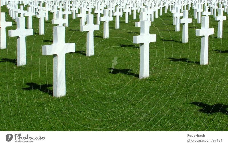 Regelmäßigkeit des Wahnsinns 1 Farbfoto Außenaufnahme Menschenleer Schatten Kontrast Erde Gras Denkmal Zeichen Kreuz Unendlichkeit historisch grün weiß Macht