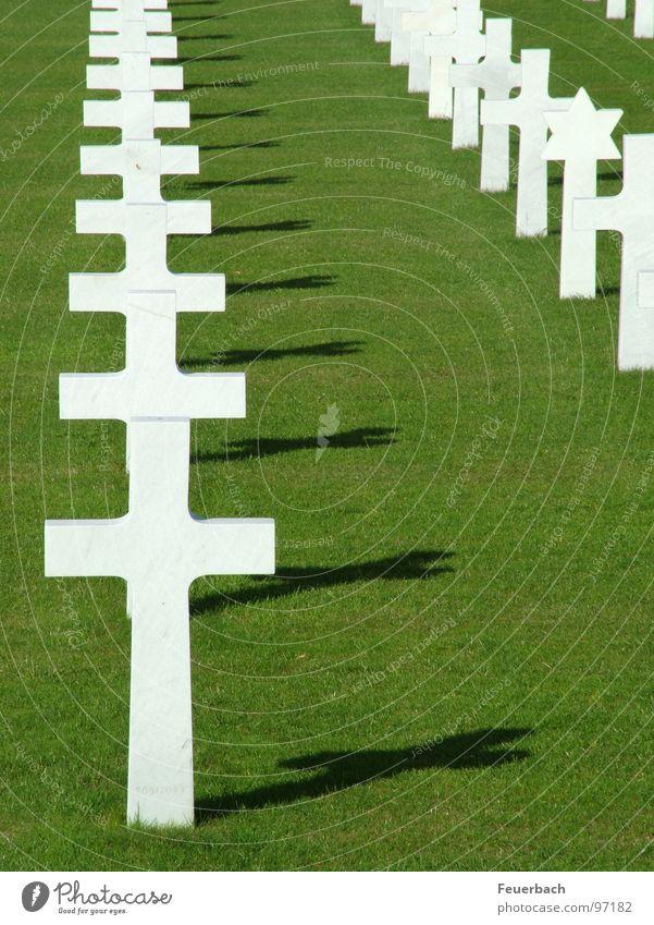 Regelmäßigkeit des Wahnsinns 2 Farbfoto Außenaufnahme Menschenleer Schatten Kontrast Gras Denkmal Zeichen Kreuz Unendlichkeit grün weiß Macht Trauer Tod Schmerz
