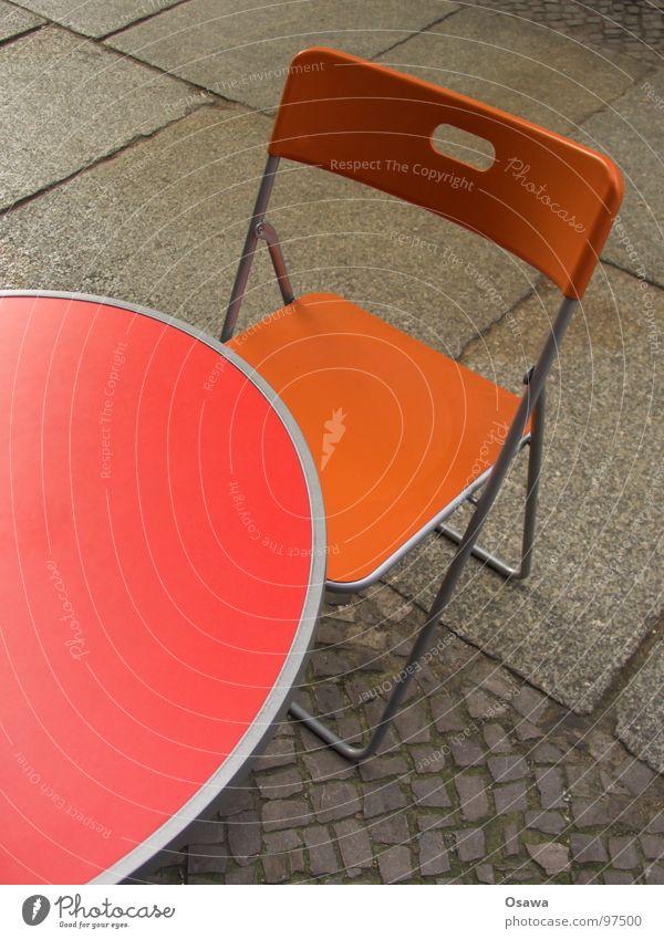 Tisch und Stuhl rot Straße orange Café Möbel Bürgersteig Kopfsteinpflaster Pflastersteine Straßencafé Campingstuhl