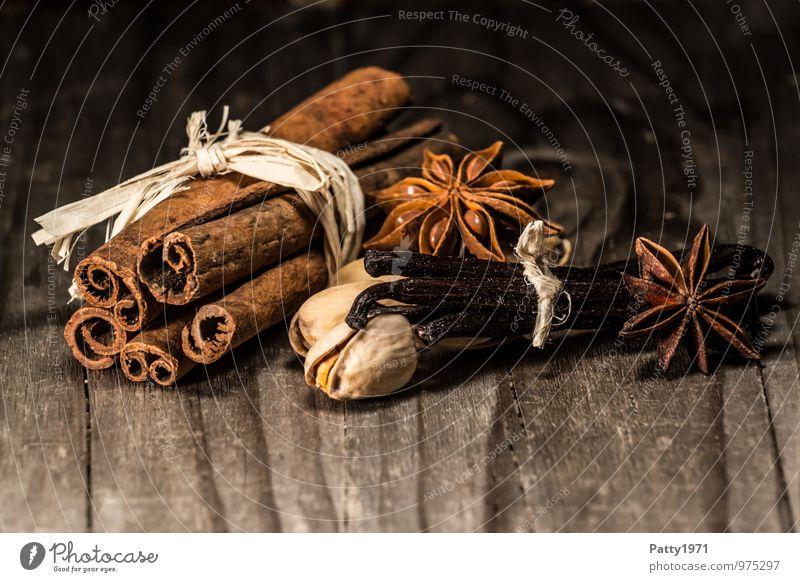 Zimt, Anis, Vaniileschoten und Nüsse liegen auf rustikalem Holztisch. Weihnachtsgewürze. Lebensmittel Kräuter & Gewürze Vanille Vanilleschote Sternanis Pistazie