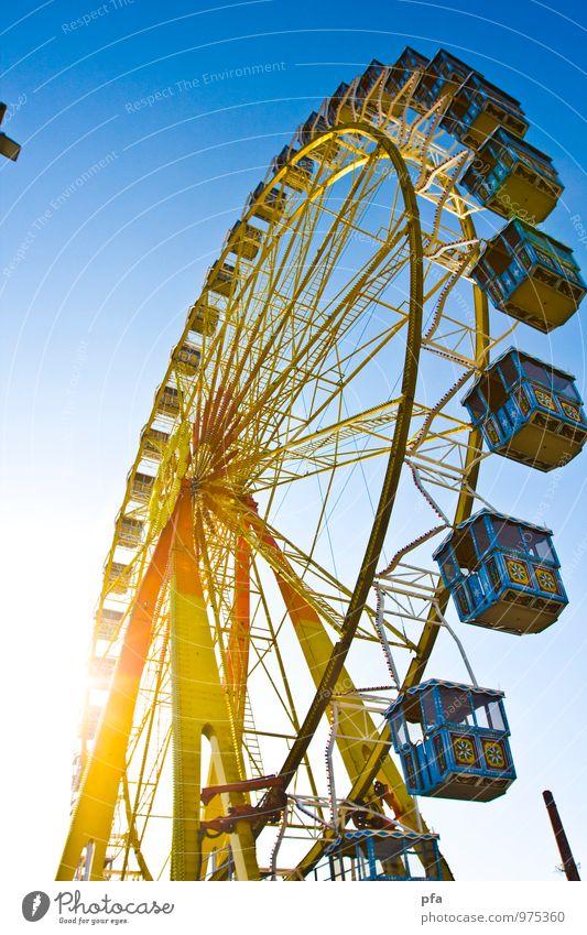 Riesenrad in der Sonne blau Sonne gelb oben frei hoch Jahrmarkt schaukeln
