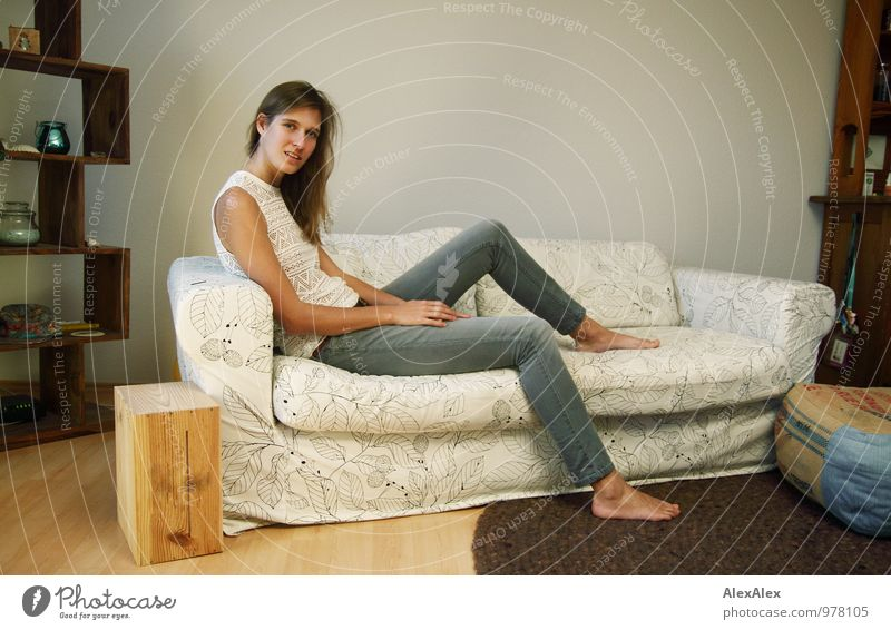 couchsurferin Wohnung Sofa Wohnzimmer Junge Frau Jugendliche Beine Barfuß 18-30 Jahre Erwachsene Jeanshose Top brünett langhaarig sitzen ästhetisch sportlich