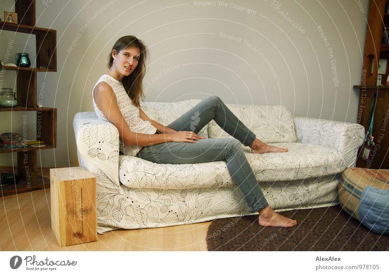 junge, große, langbeinige Frau sitzt barfuß auf einer hellen Couch Wohnung Sofa Wohnzimmer Junge Frau Jugendliche Beine Barfuß 18-30 Jahre Erwachsene Jeanshose