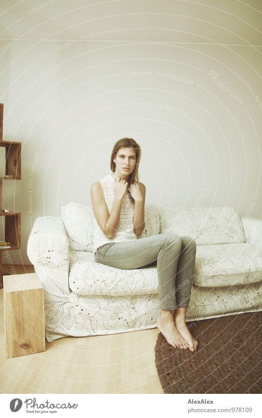 junge, große Frau sitzt auf einer hellen Couch Wohnung Möbel Sofa Junge Frau Jugendliche Körper Barfuß 18-30 Jahre Erwachsene Jeanshose Top brünett langhaarig