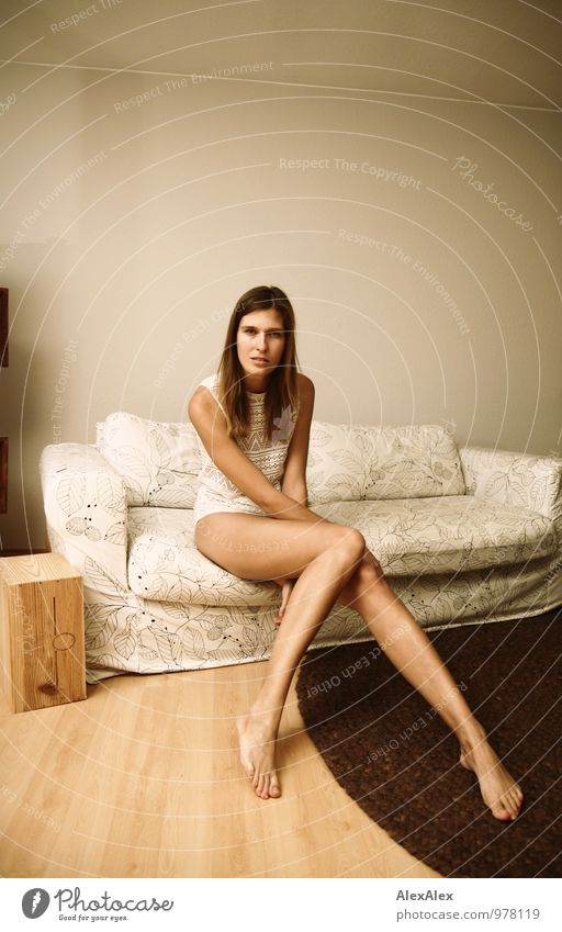große, junge, langbeinige Frau sitzt mit mit nackten Beinen barfuß auf einer hellen Couch Wohnung Sofa Wohnzimmer Junge Frau Jugendliche 18-30 Jahre Erwachsene