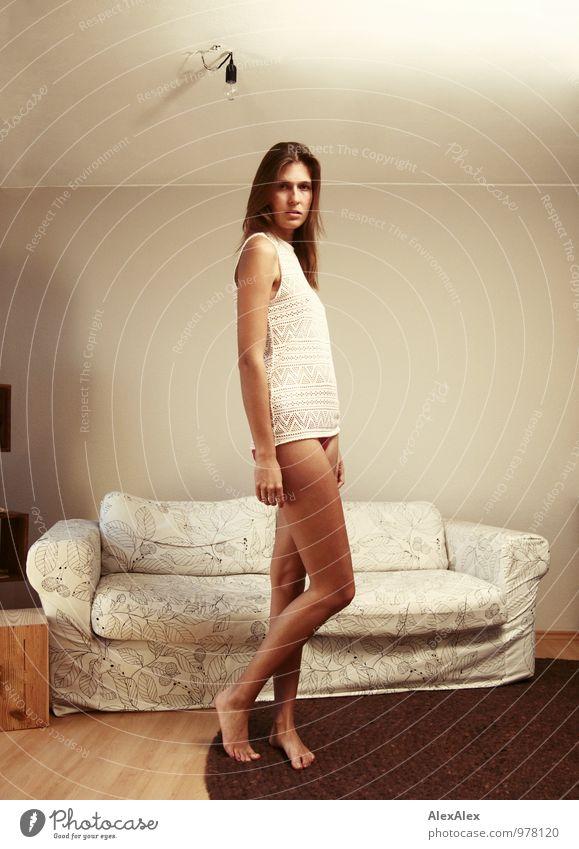 junge, große, langbeinige Frau steht barfuß mit nackten Beinen vor einem hellen Sofa und schaut in die Kamera Häusliches Leben Wohnung Wohnzimmer Junge Frau