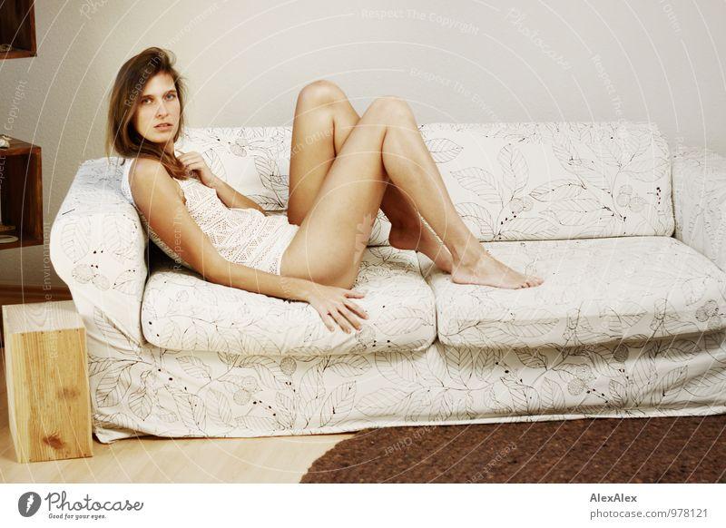 Junge, große, sportliche Frau mit langen, nackten Beinen sitzt barfuß auf einer hellen Couch Wohnung Sofa Wohnzimmer Junge Frau Jugendliche 18-30 Jahre